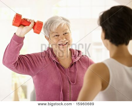 Senior woman doing dumbbell exercise with personal trainer at home, smiling.