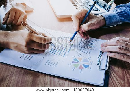 Business team analyzing income charts and graphs with modern laptop computer. Top view close up