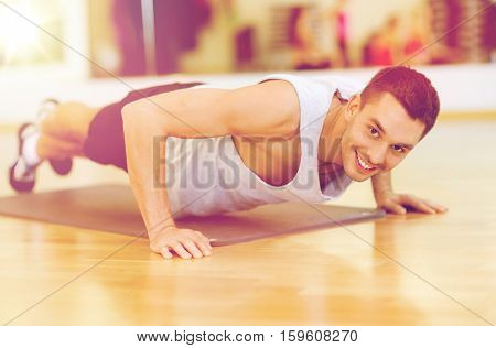 fitness, sport, training, gym and lifestyle concept - smiling man doing push-ups in the gym