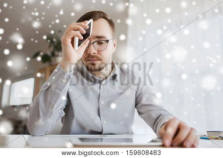 business, stress, fail, technology and people concept - businessman or creative male worker with smartphone at home office over snow
