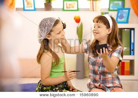 Zwei junge Mädchen Spaß mit Make-up zu Hause haben, lächelnd.?