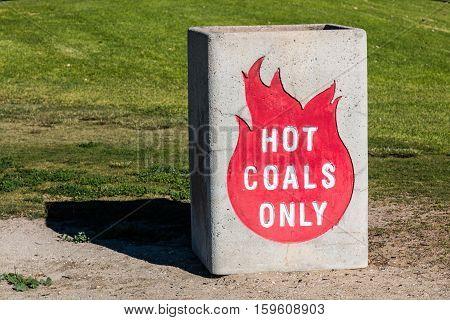 Hot coals bin near grassy area in park.