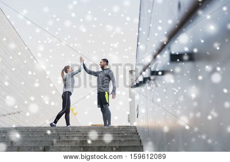 fitness, sport, people and gesture concept - smiling couple of sportsmen making high five on city street over snow