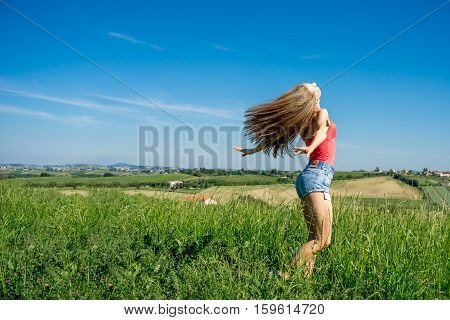 beautiful woman with open arms on meadow in country side wearing shorts and red top with bright blue sky breathing fresh air enjoying freedom