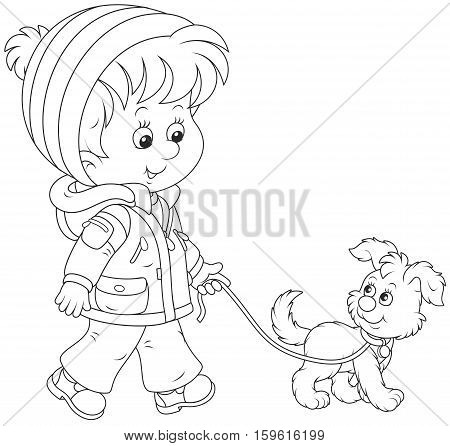 Little boy in a winter jacket and a warm hat and mittens going with his small pup