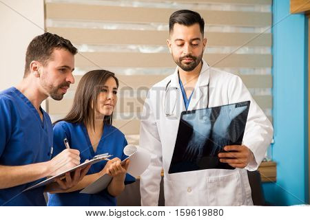 Young doctor and medical residents analyzing x-rays of a patient in a hospital room