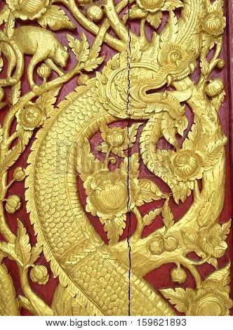 Carved big serpent motifs and tree pattern in the literature. At wall of wooden doors