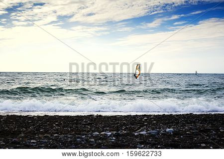 Group of windsurfers on boards in wavy sea. Lifestyle and sport completition concept. Group of people. Fun and leisure activity.