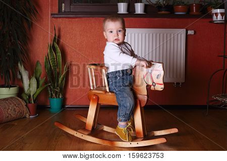 photo of cute boy riding wooden horse