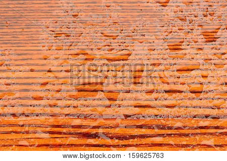 A close-up of polished natural wood texture with water drops