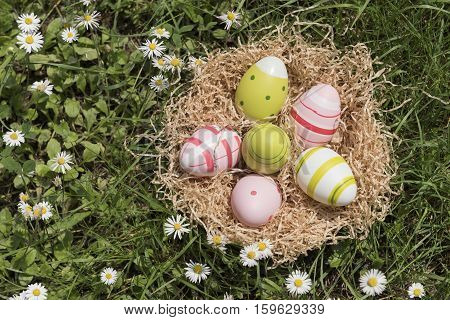 colorful easter eggs into basket on grass