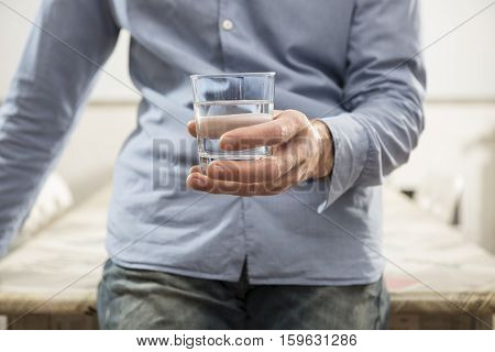man who holds in hand a glass of water