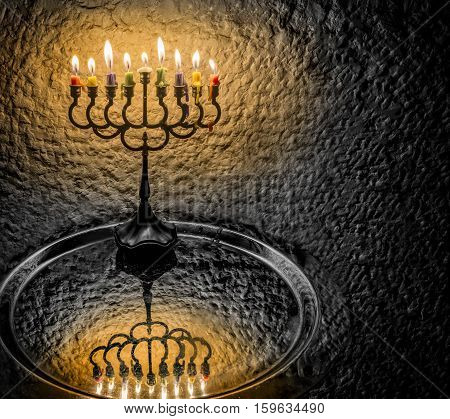 Menorah with the glitter lights of candles is traditional Jewish symbols for Hanukkah holiday. Selective focus. Low key image toned for inspiration of retro style and solemn evening ceremony
