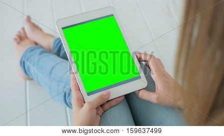 Woman sitting on the white wooden floor and using vertical tablet computer with green screen. Close up shot of woman's hands with pad. Technology and internet concept