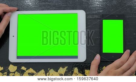 Woman looking at smartphone and digital tablet with green screen. Close up shot of woman's hands with mobile and pad
