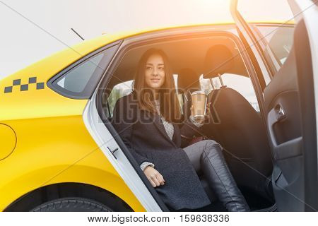 Beautiful brunette sitting in yellow taxi with door open