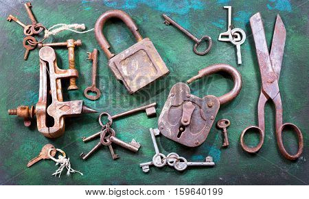 old locks keys scissors and vise on rusty background