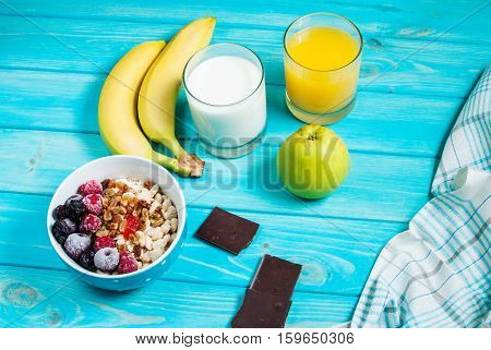 Healthy Breakfast - Oatmeal with fruits milk and juice at blue.
