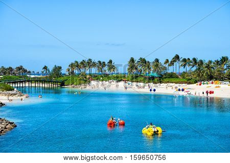 Nassau Bahamas- March 09 2016: summer beach with catamarans in water and people on vacation with blue sky and green palms on sunny coast on natural background