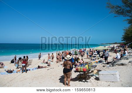 Nassau Bahamas-March 09 2016: summer beach with people sunburn on white sand during vacation with blue sky and sea water on sunny coast on natural background