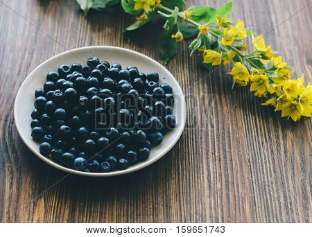 Blueberries in white ceramic plate. Wooden background suitable for text.
