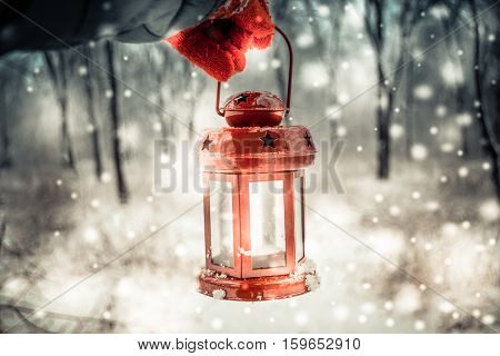 Holding in red glove a red candle lantern in the winter forest. Snow forest snowfall. Christmas Winter New Year background trembling flame Scenery. Fairy magic forest flashlight