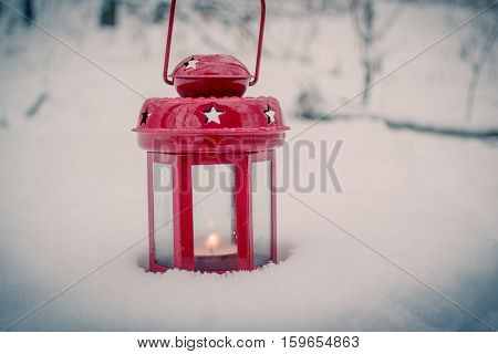 Red candle lantern with candle in snow. Christmas Winter New Year background Scenery