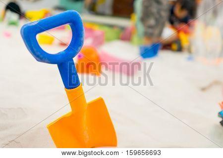 Colorful plastic shovel for children in sandbox playground.