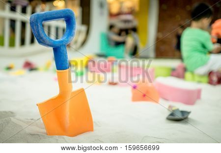 Colorful plastic shovel for children in sandbox playground.