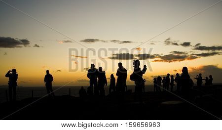 Tourists On Sounion Cape In Greece At Sunset, Making Pictures Of Famous Temple Of Poseidon. The Sout