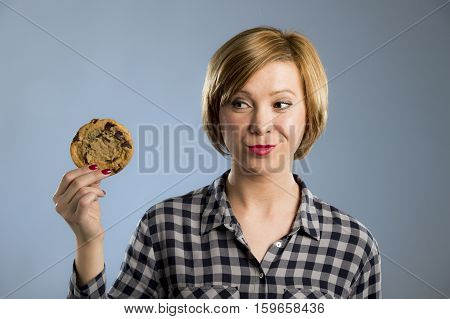 young blond cute and friendly caucasian woman in casual clothes holding big delicious chocolate cookie looking with temptation as thinking if ignoring diet and eating sweet junk food isolated background