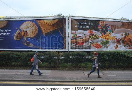 Bracknell,England - December 02, 2016: People walking by in front of large billboards advertising Christmas food and groceries on a cloudy December day in Bracknell, England