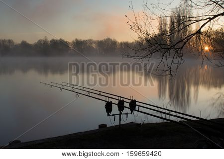Sunrise over a lake with a silouhette of carp fishing rods