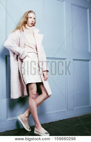 young blonde teenage girl in fur coat, fashion dressed model, studio shot modern hipster close up