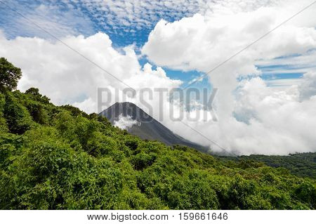The perfect peak of the active and young Izalco volcano seen from a view point in Cerro Verde National Park in El Salvador. Nearly covered with thick white clouds. Central America