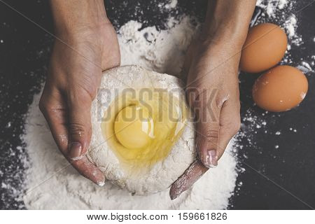 Top view of dough with a broken egg and woman's hands holding it. Concept of making your own bread