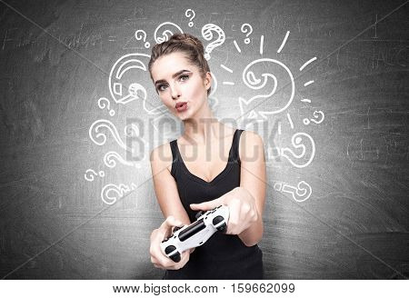 Geeky teenager girl is holding a video game controller and standing near a blackboard with question marks