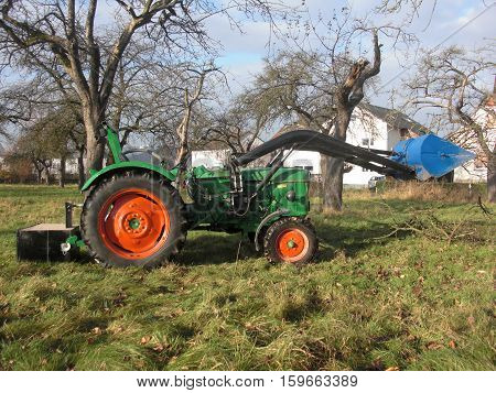 Tractor working in the garden  Works in public park Tractor tree branches Environment cleaning concept