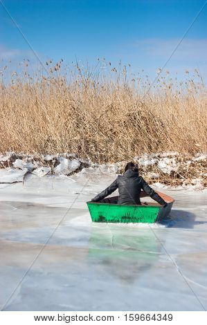 Winter time. The man in the boat on ice. The river covered with ice.