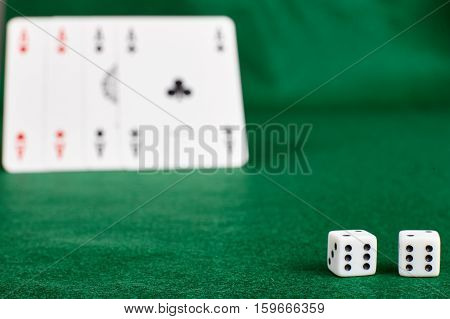 White dices and four aces on green table.Ιllegal gambling.