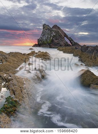 Sunrise with lovely red clouds at bow fiddle rock near Portknockie