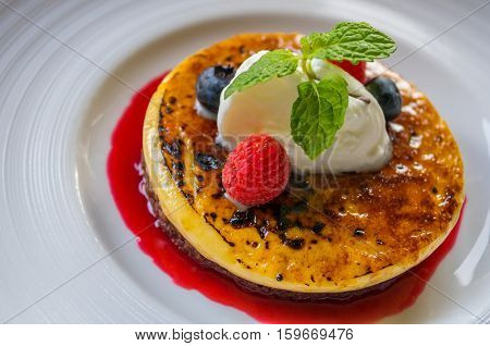 Rasberry pancakes with jam and mint on plate