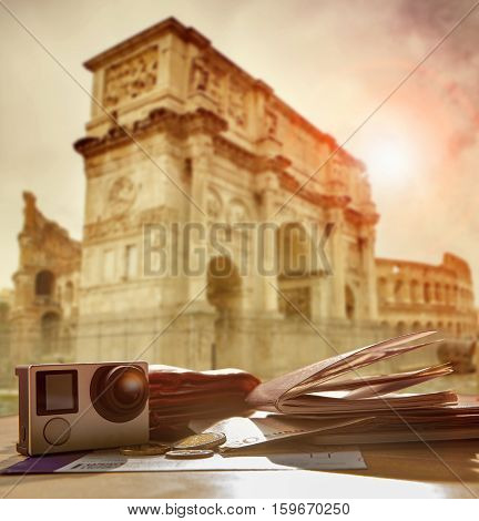 passport traveling boarding pass euro money and easy camera on wood table against sun light at Arch of Constantine colosseum rome italy