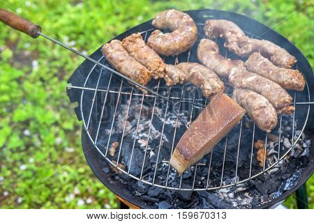 Roasting of sausages and lard on grill