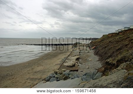A promenade and sea defences crumbling and falling on to the beach below. Showing erosion on the east coast of England. Background of the cliffs and caravans close to the cliff edge with sea and grey sky.