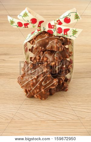 A stack of star shaped German Gingerbread with almonds decorated with a cute Christmas ribbon isolated on light brown wooden background.
