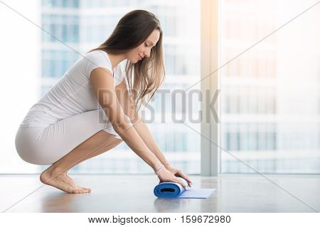 Young woman, wear comfortable athletic clothing in a modern apartment unrolling yoga mat, preparing a cozy place before practice in class or at home. Full length. Healthy lifestyle concept