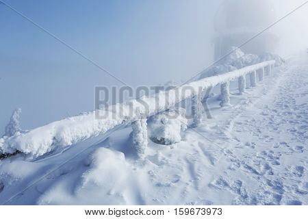 Winter landscape and wooden railings with frosted snow in fog in fog in Sumava Czech republic