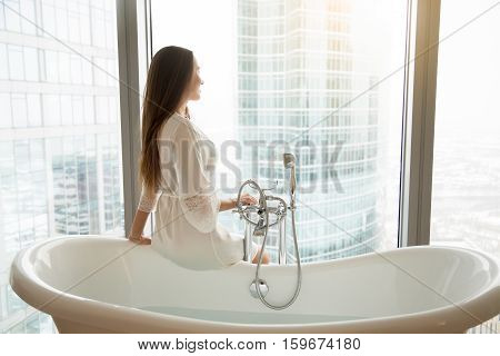 Profile portrait of young model in a gown sitting at the side of freestanding white bath, bathroom design, luxury sanitary ware collection, preparing relaxing bath. Beauty, healthy lifestyle concept