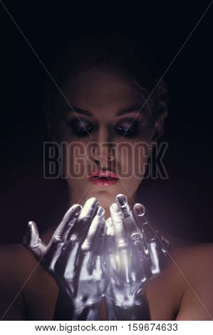 Close up portrait of beauty cyber woman from the future with clay hairstyle and silver hands